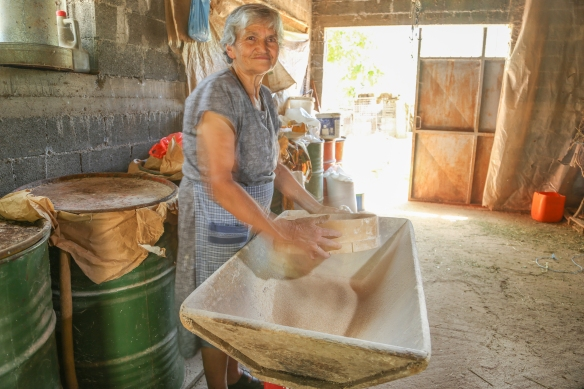 Thomae sifting flour from wheat grown and milled in her village of Vaskina.